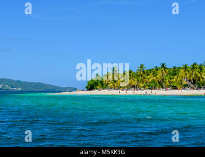 Beautiful beach with palms blue sky and turquoise water, some tourists having fun, relaxing and swimming in the - Stock Photo