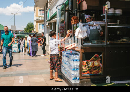 Istanbul, June 11, 2017: Editorial image of little boy buying gyros from street vendor and man in green shirt is - Stock Photo