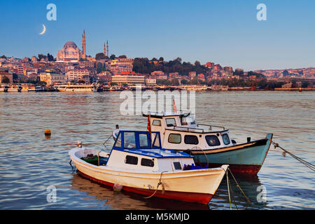 View over Suleymaniye Mosque in the Golden Horn with crescent moon in the sky, Istanbul, Turkey. - Stock Photo