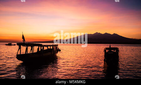 The sunrise above the volcano in Bali from the Gili Islands can be seen with two boats in the foreground - Stock Photo
