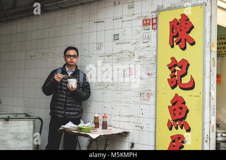 A man is eating his noodles next to a shop in an alleyway in Hong Kong - Stock Photo