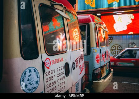 The reflection of the shops is seen in the back window of two minibuses in Hong Kong - Stock Photo