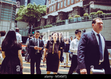 Commuters cross the road near the HSBC building in Hong Kong - Stock Photo