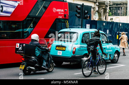 A deliveroo scooter, black cab taxi, cyclist and red London bus are lined up waiting at the traffic lights. - Stock Photo