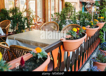 View of empty open summer cafe with wicker chairs and wooden furniture next to pots with plants and flowers. Empty - Stock Photo