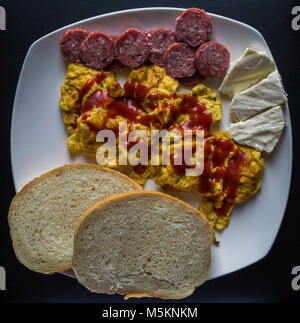 Scrambled eggs with ketchup with bread, salami  and cheese - Stock Photo