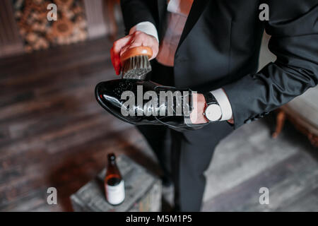Cleaning shoes on wooden background. black shoe with a brush - Stock Photo