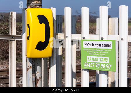 Sign for the Samaritans charity next to an emergency telephone callbox at a railway crossing in Berkshire, England, - Stock Photo