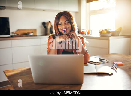 Smiling young African female entrepreneur sitting at her kitchen table using a laptop while working from home - Stock Photo