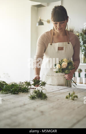Young female florist standing at a table in her flower shop putting together a bouquet of roses - Stock Photo