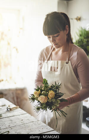 Young female florist putting together an arrangement of mixed flowers while working at a table in her flower shop - Stock Photo