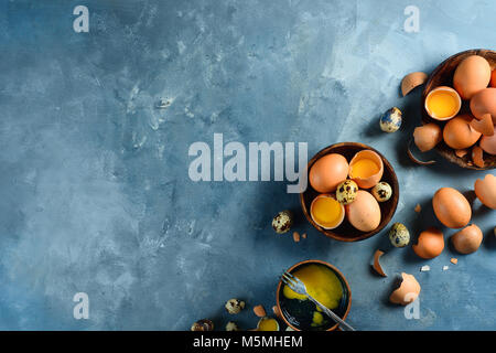 Header with raw brown hen and quail eggs, whole and broken, on two wooden dishes. Concrete background with copy - Stock Photo