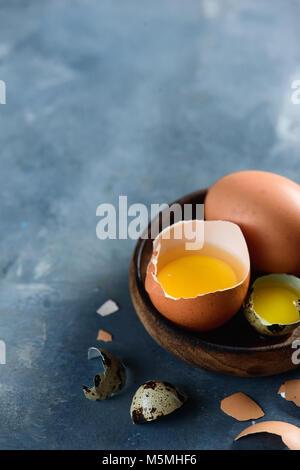Yolk in an eggshell close-up. Raw cooking ingredients background with copy space. Modern Easter concept with brown - Stock Photo