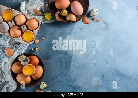 Header with raw brown hen and quail eggs, whole and broken, on a wooden dish and carton tray. Concrete background - Stock Photo