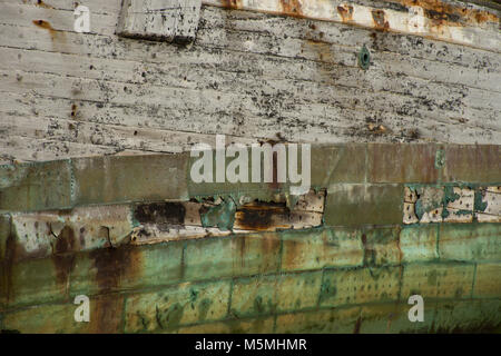 Close up of weathered wood and rusted, oxidized metal planks on a shipwrecked boat in the Falkland Islands. - Stock Photo