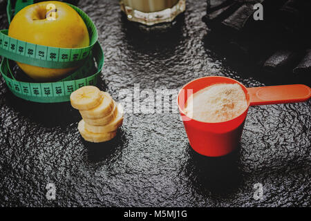 Protein powder in scoop and fruits on stone table - Stock Photo