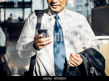 Businessman using mobile phone to chatting with friend after work at corridor office building,selective focus on - Stock Photo