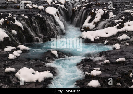 Blue Bruarfoss waterfall in winter in Iceland - Stock Photo