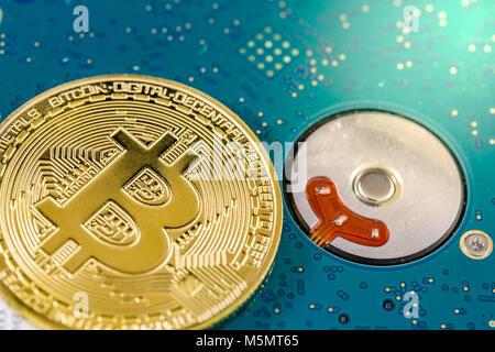Single golden bitcoin on harddisk close image - Stock Photo