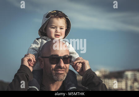 Portrait of a father carrying his cute little son on shoulders, baby and daddy with pleasure spending time together - Stock Photo