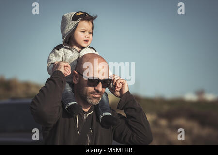 Portrait of a father carrying his cute little son on shoulders, baby and dad with pleasure spending time together - Stock Photo
