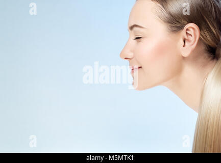 Closeup profile portrait of a nice blond girl with closed eyes isolated on blue background, conceptual photo of - Stock Photo