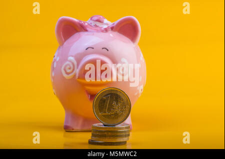 Piggy bank and one euro on a pile of coins. Yellow background. Cover. Euro money. Currency of the European Union. - Stock Photo