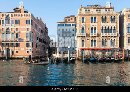Tourists enjoying a gondola ride on the Grand Canal at sunset, Venice, Veneto, Italy passing the Hotel Bauer Palazzo - Stock Photo