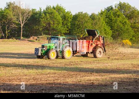 Farmer spreading organic fertiliser, fertilizer  or manure on a spring pasture using a Degullaume muck spreader - Stock Photo
