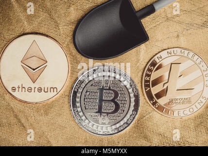 Silver bitcoins ,litecoin,ethereum crypto coin with black shovel mining on golden rough ground texture,Cryptocurrency - Stock Photo