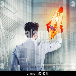 Businessman drawing a rocket. Concept of business improvement and enterprise startup - Stock Photo