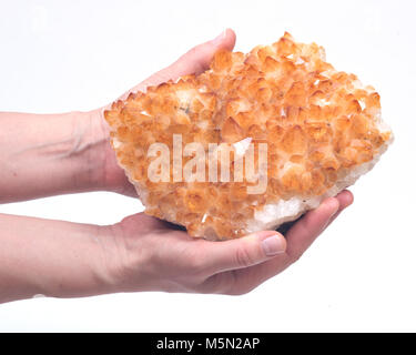 Citrine druzy cluster in woman's hand isolated on white background - Stock Photo