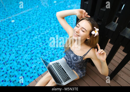 happy woman rest after hard work at swimming pool with laptop, d - Stock Photo