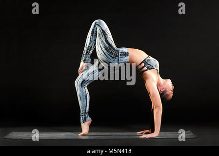 Fit healthy woman doing a one legged wheel pose while working out on a yoga mat arching her back gracefully with - Stock Photo