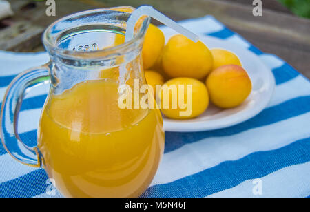 apricot juice in a Glass jug with straw and fruit on napkin - Stock Photo