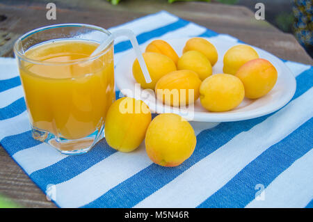 apricot juice in a Glass with straw and fruit on napkin - Stock Photo