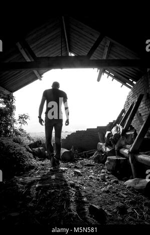 Location Portrait Photography of a male in a derelict barn. Photographer Claire Allen - Stock Photo