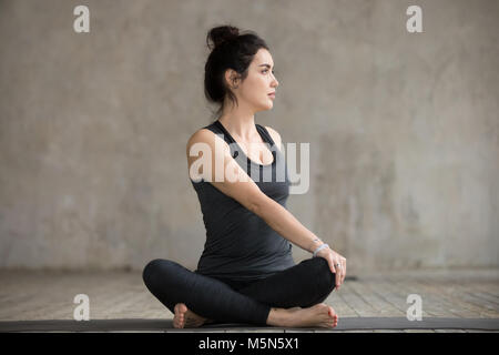 woman practicing yoga doing revolved chair pose
