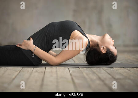 Young sporty woman practicing yoga, doing Matsyasana exercise, Fish pose, working out, wearing sportswear, black - Stock Photo