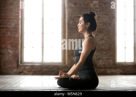 Young sporty woman practicing yoga, doing Padmasana exercise, Lotus pose, working out, wearing sportswear, black - Stock Photo