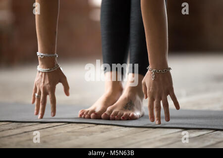 Young sporty woman practicing yoga, doing Head to knees pose, Uttanasana exercise, working out, wearing wrist bracelets, - Stock Photo