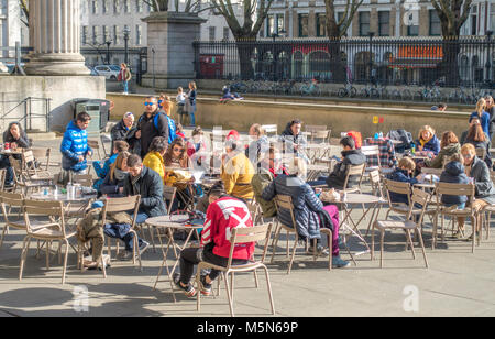 People at cafe tables outside The British Museum (dedicated to human history, art and culture), on a sunny February - Stock Photo