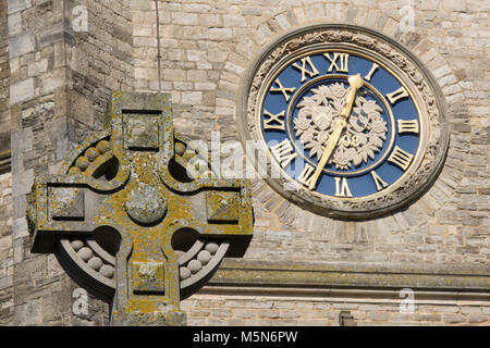 a church clock and celtic cross made of stone outside of a religious building on the isle of wight. places of worship - Stock Photo