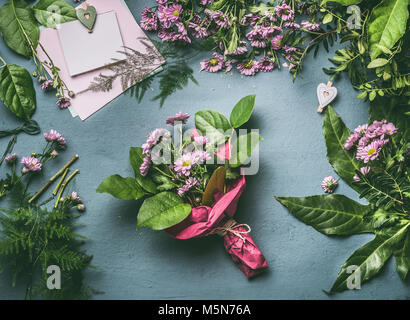 Florist wrapping flowers in paper at flower shop stock photo desk table with bouquet of flowers wrapped in red wrapping paper florist workspace with various mightylinksfo Gallery