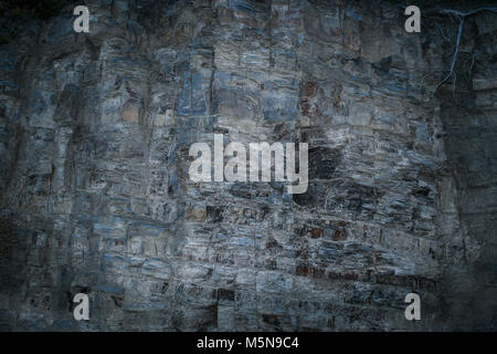 Grunge mystical gray-blue layered rock wall with uneven surface. - Stock Photo