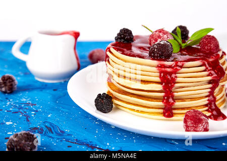 American pancake with jam and frozen raspberry with tea on blue background. Close up. - Stock Photo