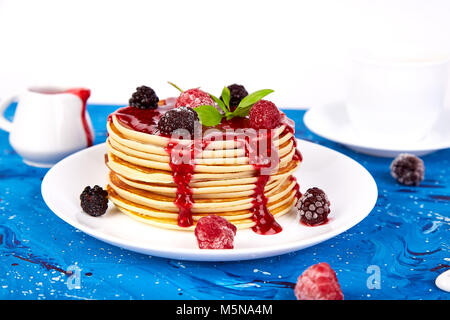 American pancake with jam and frozen raspberry with tea on blue background. - Stock Photo