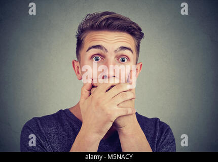 Portrait of a young anxious man with shocked scared face expression looking at camera - Stock Photo