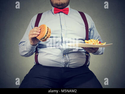 Crop shot of big man in formal clothes sitting and consuming plate with fast food on gray. - Stock Photo