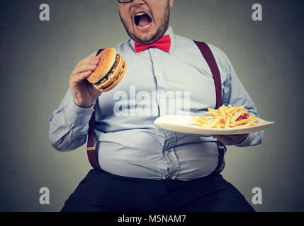 big man in formal clothes sitting and consuming plate with fast food on gray. - Stock Photo